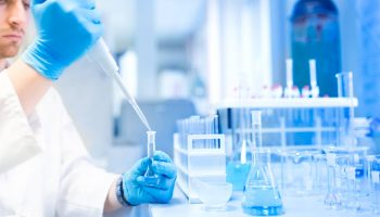 Test tubes in clinic, pharmacy and medical research laboratory with male scientist using pipette